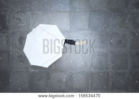 Top view of a woman hidden under white umbrella and checking if it's raining