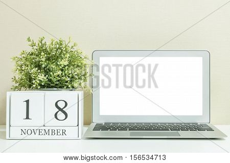 White wooden calendar with black 18 november word with white blank space at center of computer notebook on white wood desk and cream wallpaper textured background selective focus at the calendar