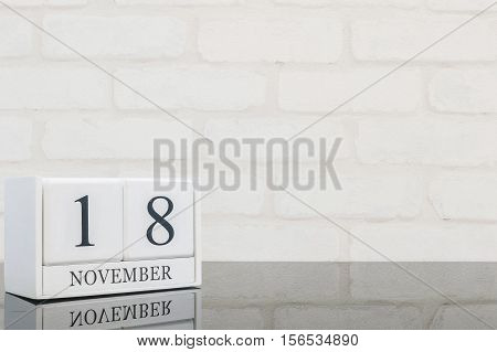 Closeup white wooden calendar with black 18 november word on black glass table and white brick wall textured background with copy space selective focus at the calendar