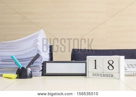 Closeup white wooden calendar with black 18 november word on blurred brown wood desk and wood wall textured background in office room view with copy space selective focus at the calendar