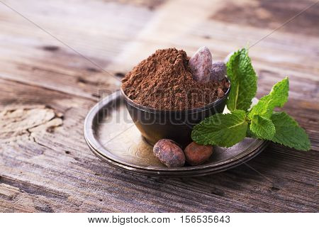 Cocoa powder and beans dry ripe cocoa vintage metal German silver dish with a sprig of fresh fragrant mint on a simple wooden background. selective focus. Room for text