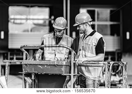 Construction worker operating on construction machine, black and white