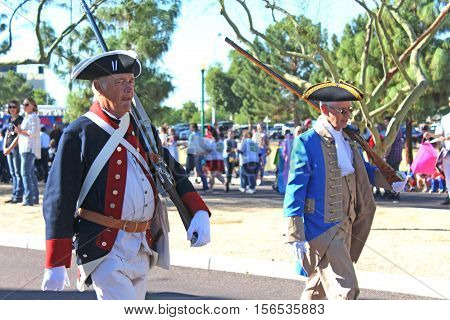 Surprise, AZ, USA - NOV. 11: Two males dressed up as Revolutionary war heroes holding muskets while marching in the city of Surprise, Arizona Veteran's Day Parade November 11, 2016