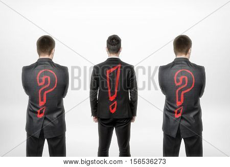 Back view of three businessmen with question mark and exclamation one in the center. Leader and leadership. Business concept and idea. To have your own opinion. Innovator ideas.