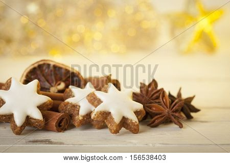 Closeup of cinnamon stars christmas cookies with cinnamon quills, star anise and dried oranges