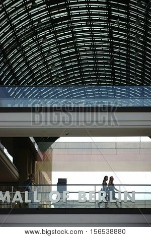 BERLIN, GERMANY - JUNE 21: Guests and visitors go over a bridge with Glass railings under the roof of the Mall of Berlin on June 21 2016 in Berlin.