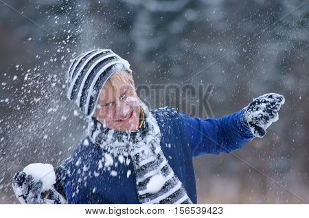 The satisfied boy merrily plays snowballs on fresh air.