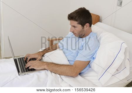 young businessman intern as patient in hospital suffering disease and working at the clinic bed with laptop computer in workaholic concept