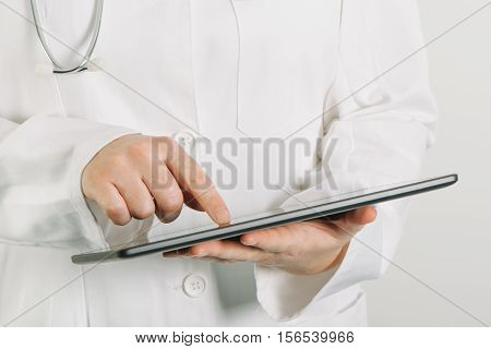 Female doctor in white uniform using tablet computer in hospital office