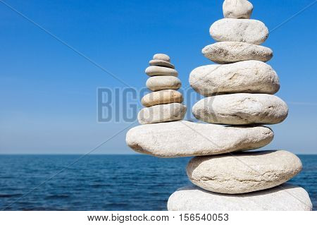 Concept of balance and harmony. White rocks zen on the sea
