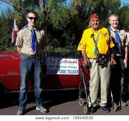 PHOENIX, AZ, USA - NOV. 11: Two adolescent boy scouts stand with Joe Kellwood a veteran Navajo Code Talker  in front of a red convertible with a sign that says Joe Kellwood US Marine Corp  Navajo Code Talker at the city of Phoenix, Arizona Veterans Day Pa