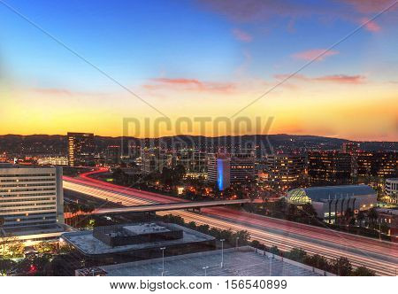 Sunrise over a highway in Irvine, California as headlight trails move through the roadways.