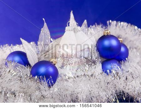 Blue New Year's balls and tinsel on a blue background