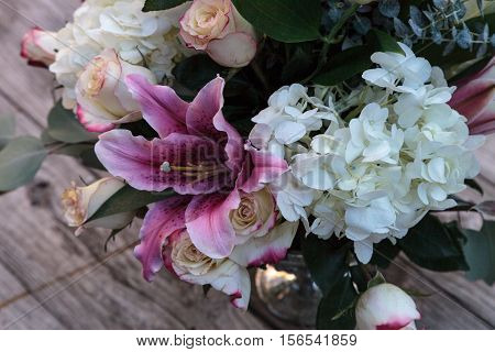 Wedding bouquet of white and pink flowers including roses, hydrangea, star gazer lilies and queen annes lace on a rustic table in the French countryside on Valentine's Day