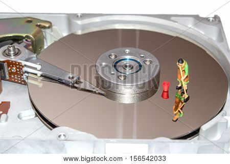 Cleaning the hard disk. A woman cleans a HDD. Figurine of a woman. Cleaners. Cleaning of computer element. Recovery of computer data. Miniature people repair the hard drive