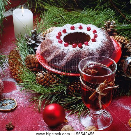 Christmas table setting. Bundt cake pudding sprinkled with sugar powder decorated with and mulled wine.