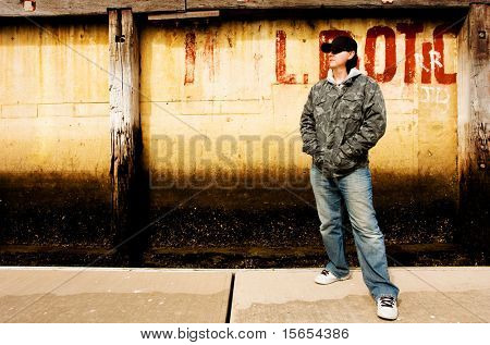 A Skateboarder stands in front of a dirty wall