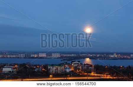 View of early moon in blue evening sky with reflection in the river. Background