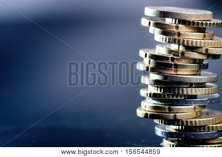Euro money. Coins are isolated on a dark background. Currency of Europe. Balance of money. Building from coins.