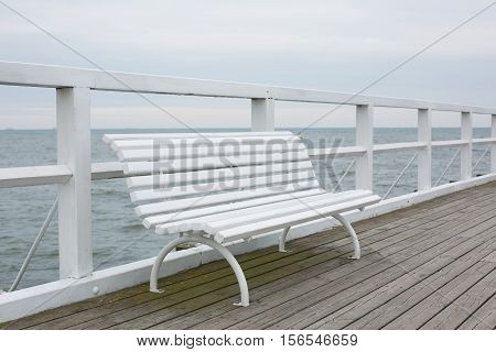 White bench on a wooden pier on the seashore