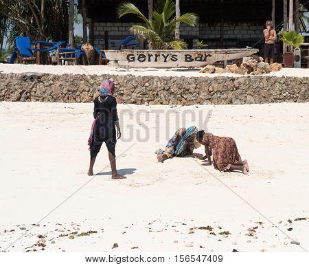 Zanzibar, Tanzania - July, 14, 2016: Editorial use - local african girls seeking something on sandy beach near bar in Zanzibar
