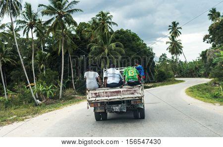 Zanzibar, Tanzania - July, 14, 2016: truck with people on backdrop driving on rural african road in Zanzibar