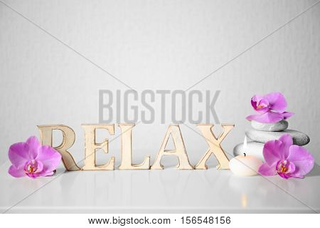 Word RELAX made of wooden letters and spa composition on table