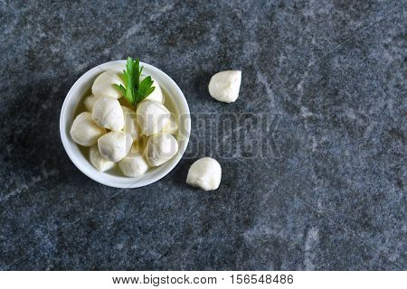 Mini mozzarella with herbs on a concrete background. Top view.