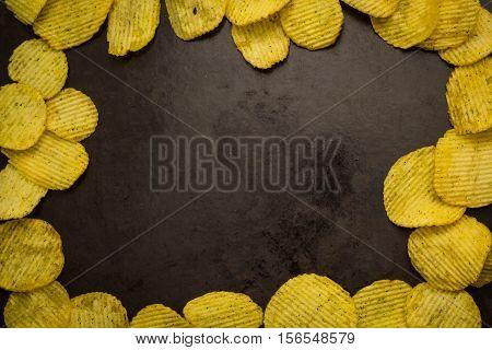 potato chips on a dark background. copy space
