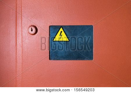 Sign of danger of electrical shock placed on viewing window next to lock of orange switch box