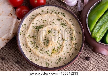 Humus in homemade bowl chapati and vegetable in top View.