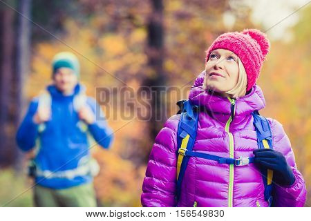 Happy couple hikers trekking in beautiful yellow autumn forest and mountains. Young people man and woman walking on trek trail with backpacks healthy lifestyle adventure camping on hiking trip.
