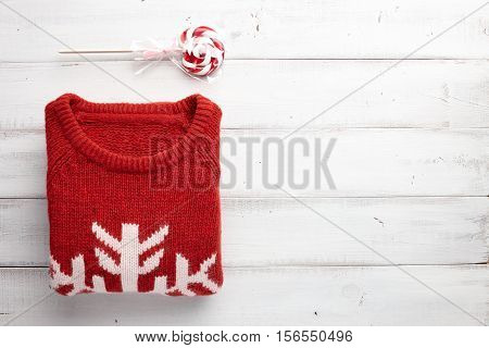 Winter holiday knitted sweater and christmas lollipop on white wooden background.