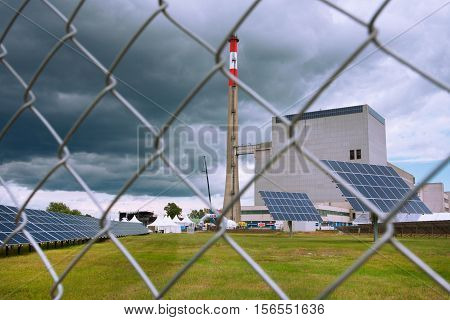 ZWENTENDORF, AUSTRIA - MAY 31, 2013: Solar panels against the building of Zwentendorf Nuclear Power Plant on May 31, 2013 in Austria. The atomic power plant was built in 1976 with a hot water reactor