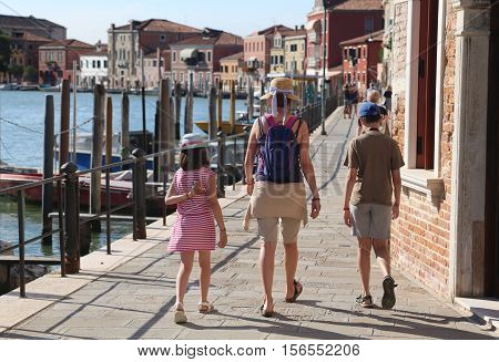 Family With Mom And Two Children Walking On The Island Of Murano