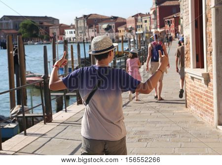 boy with thumbs up while walking with family on the island of Murano near Venice in Italy