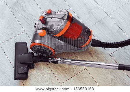 vacuum cleaner with orange color on gray laminate