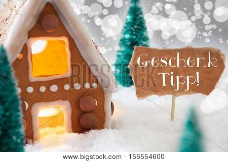 German Text Geschenk Tipp Means Gift Tip. Gingerbread House In Snowy Scenery As Christmas Decoration. Trees And Candlelight For Romantic Atmosphere. Silver Background With Bokeh Effect.