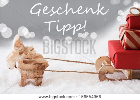 German Text Geschenk Tipp Means Gift Tip. Moose Is Drawing A Sled With Red Gifts Or Presents In Snow. Christmas Card For Seasons Greetings. Silver Background With Bokeh Effect.