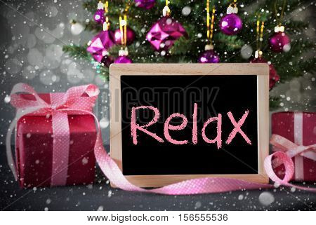 Christmas Tree With Rose Quartz Balls, Snowflakes And Bokeh Effect. Gifts Or Presents In The Front Of Cement Background. Chalkboard With English Text Relax
