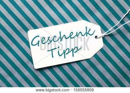 German Text Geschenk Tipp Means Gift Tip. One Label On A Turquoise Striped Wrapping Paper. Textured Background. Tag With Ribbon.