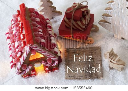 Label With Spanish Text Feliz Navidad Means Merry Christmas. Gingerbread House On Snow With Christmas Decoration Like Trees And Moose. Sleigh With Christmas Gifts Or Presents.