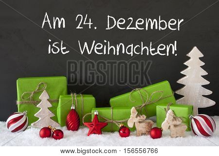 German Text Am 24. Dezember Ist Weihnachten Means December 24th Is Christmas Eve. Green Gifts With Decoration Like Tree, Moose Or Red Christmas Tree Ball. Black Cement Wall As Background With Snow.