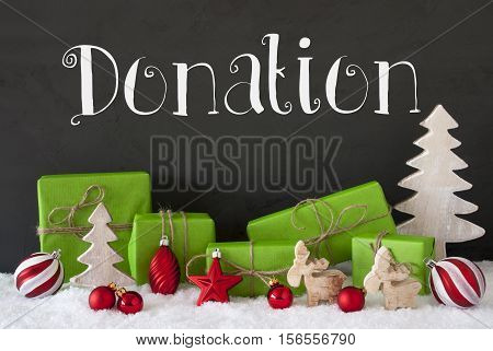 English Text Donation. Green Gifts With Christmas Decoration Like Tree, Moose Or Red Christmas Tree Ball. Black Cement Wall As Background With Snow.