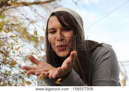 A young woman blowing into empty hand