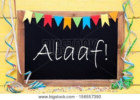 Blackboard With German Text Alaaf Means Happy Carnival. Party Decoration Like Streamer And Confetti. Yellow Wooden Background. Greeting Card For Celebrations