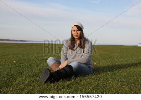 A young lady with a walking boot cast sits in the grass.