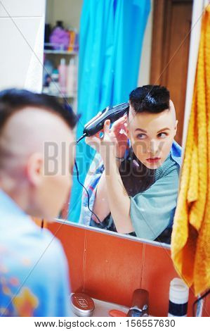 Young cute girl shaves her hair on the head near the mirror in the bathroom