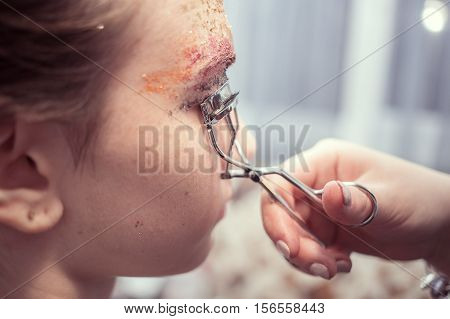 young woman making curl eyelashes in salon