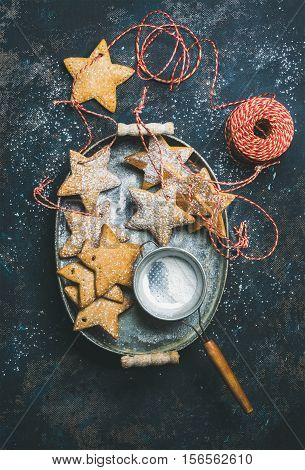 Christmas holiday star shaped gingerbread cookies for Christmas tree decoration and sieve in metal tray over dark blue background, top view